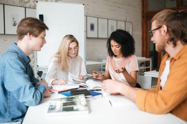 テーブルに座って、オフィスで一緒に働いている若者のグループ。思慮深く何かを議論している2人のかわいい女の子と2人の男の子の肖像画