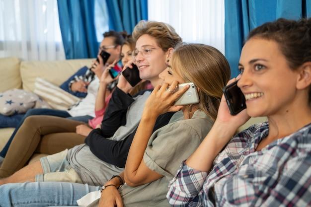Группа молодых людей, сидящих в ряд на диване, разговаривают по мобильным телефонам