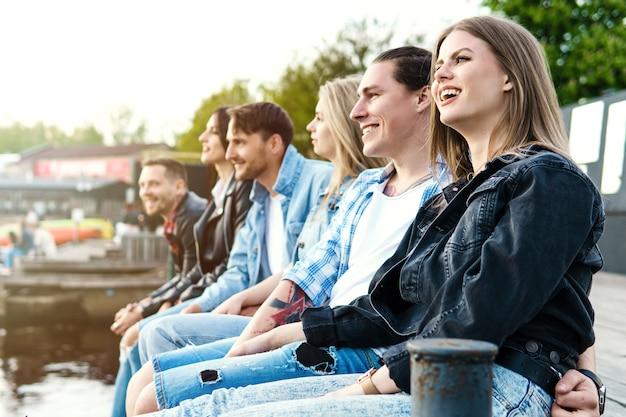 Группа молодых людей, сидящих на пирсе у реки