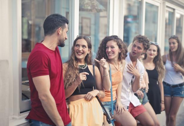 通りに立ちながら笑っている若い人たちのグループ