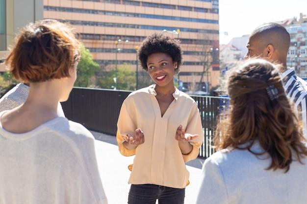 通りに立っているとコミュニケーションの若い人たちのグループ