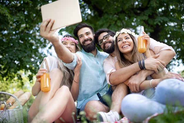 Группа молодых людей, делающих селфи на открытом воздухе, пикник, весело
