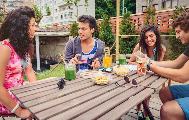 屋外での余暇の夏の日に健康的な飲み物を飲みながらテーブルの周りで話したり笑ったりする若者のグループ
