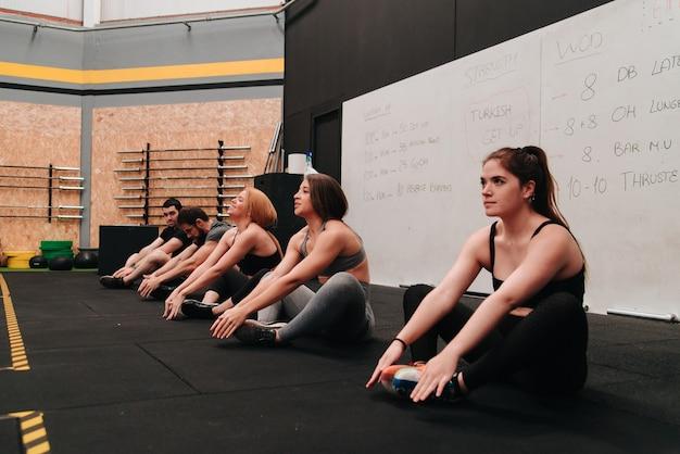 Группа молодых людей тренируется, делая приседания в их распорядке упражнений.