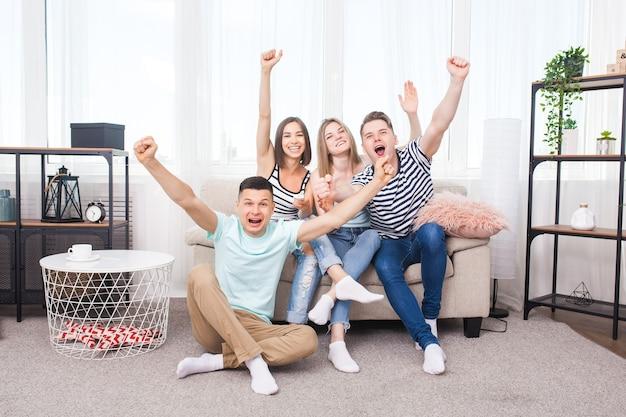 Tv를 시청하는 젊은 사람들의 그룹입니다. 재미 있고 실내에서 게임을 보는 감정적 인 친구.