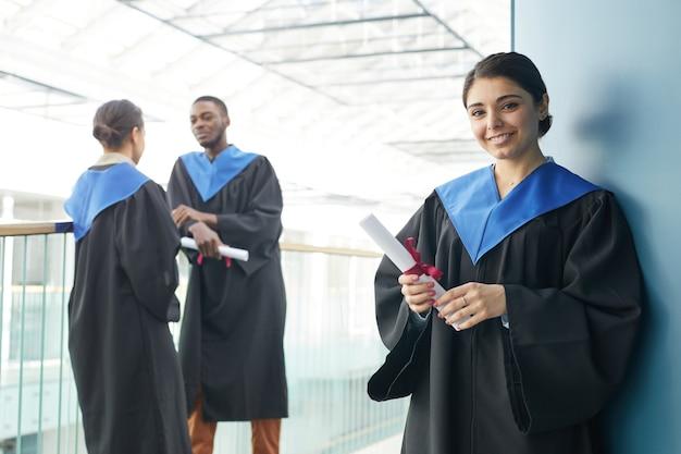 現代の大学のインテリアの屋内で卒業式のガウンを着ている若者のグループは、卒業証書を保持し、前景、コピースペースでカメラを見て笑顔の中東の女性に焦点を当てています