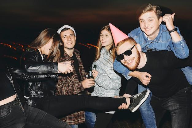 시골에서 어두운 밤에 크리스마스를 축하하는 재미 흰색 맥주 병을 가진 젊은 사람들의 그룹