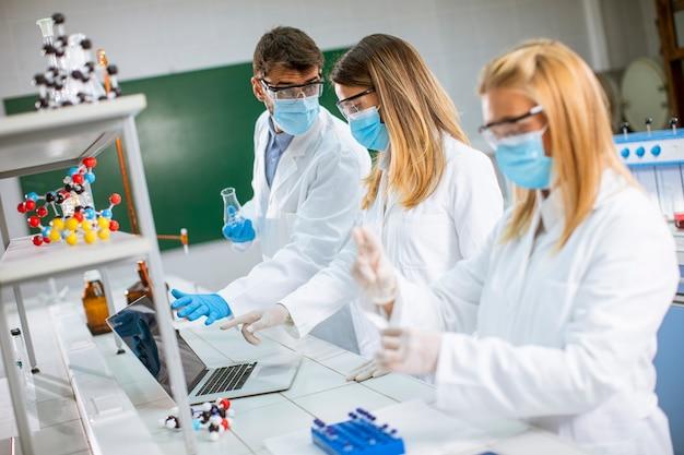 研究室で化学データを分析する若い研究者のグループ