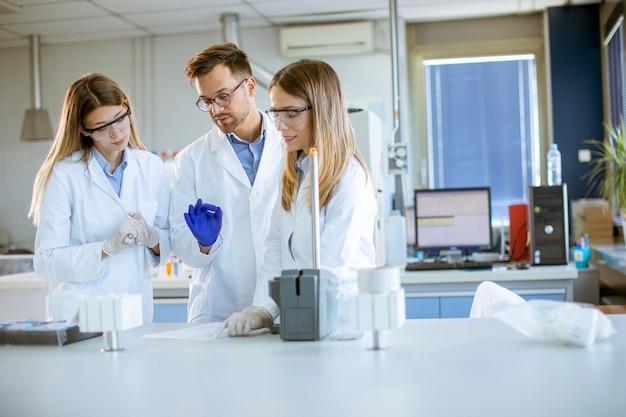 Группа молодых исследователей в защитной спецодежде стоит в лаборатории и анализирует пробы жидкости на оборудовании ионной хроматографии