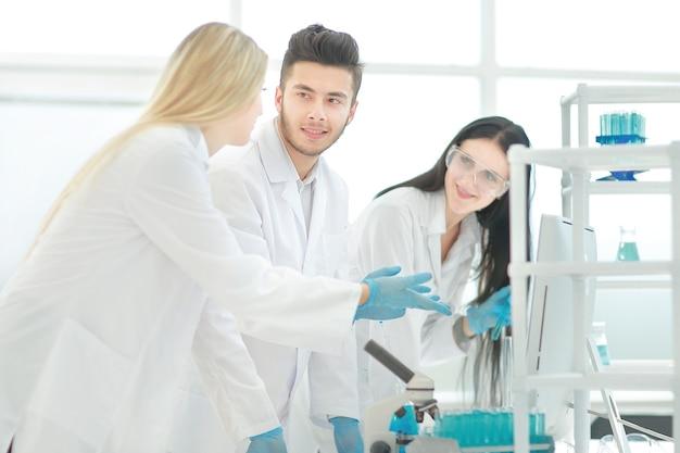 研究室で何かについて話し合っている若い科学者のグループ