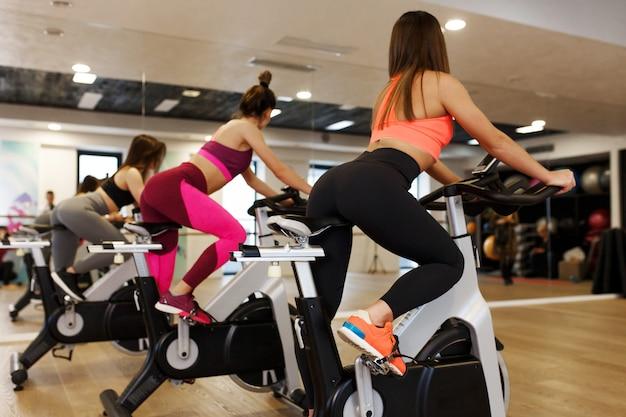 ジムでエアロバイクで若いスリムな女性のワークアウトのグループ。スポーツとウェルネスライフスタイルのコンセプト