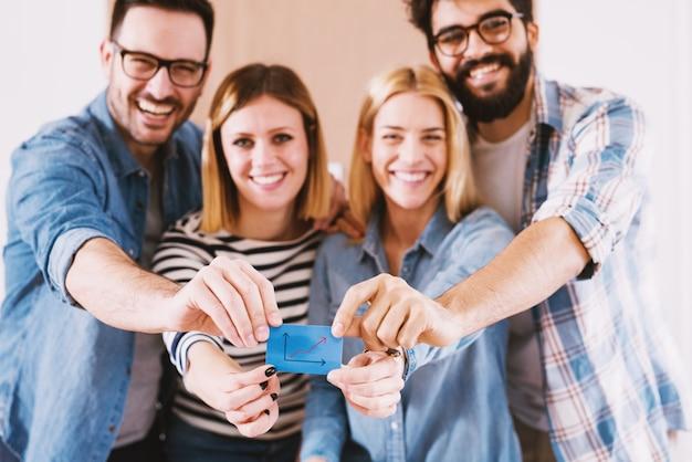 Группа молодых улыбающихся дизайнеров, держащих синюю наклейку.