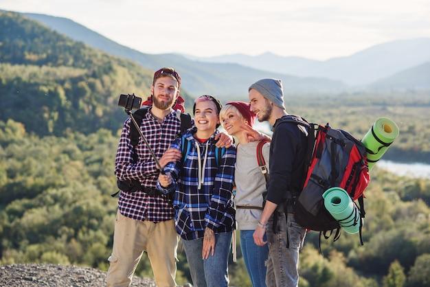 산에서 함께 여행하는 젊은 웃는 사람들의 그룹입니다.