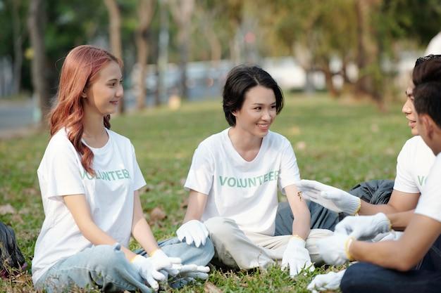 도시 공원에서 쓰레기를 수거한 후 풀밭에 앉아 이야기를 나누는 웃고 있는 젊은 자원 봉사자 그룹