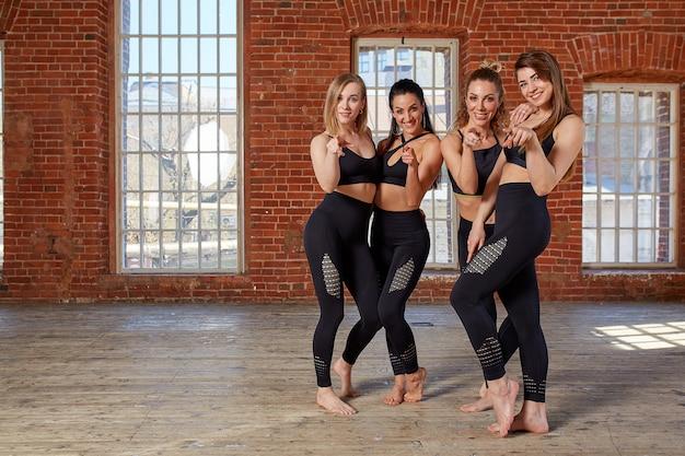 広々としたロフトスタジオでのトレーニングの後休んでいる若いスポーツ少女のグループ。ジムでの女性の友情、屋内、フィットネス後の太陽のまぶしさ効果。