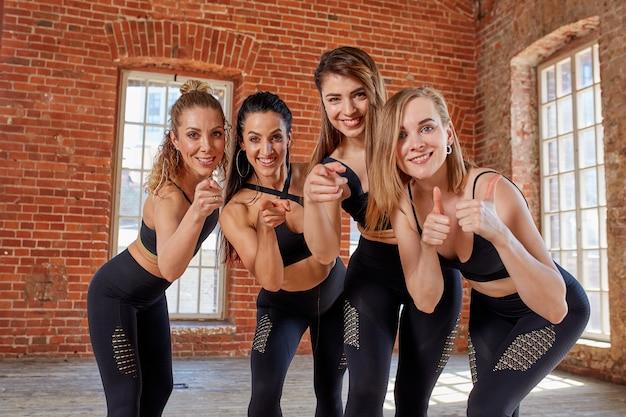 広々としたロフトスタジオでのトレーニングの後休んでいる若いスポーツ少女のグループ。ジムでの女性の友情、フィットネス後のリラックス、屋内、太陽のまぶしさの効果。