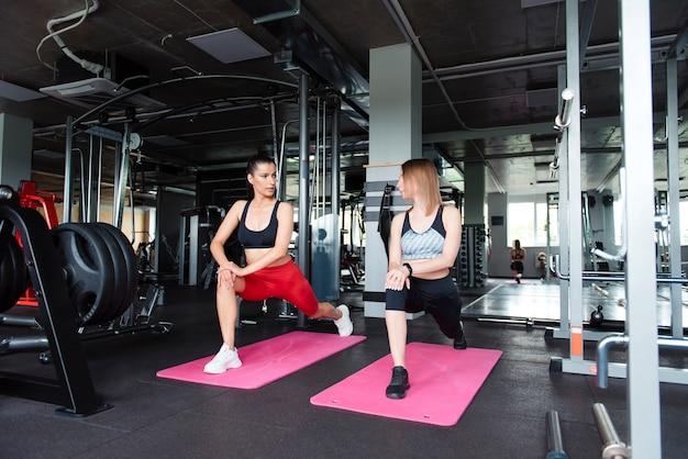 ヨガマットで脚を伸ばすスポーツウェアの若い強い女性のグループ