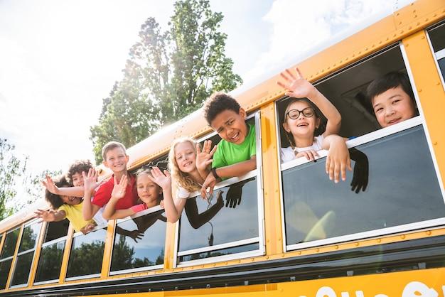 노란색 스쿨 버스를 타고 초등학교에 다니는 어린 학생들의 그룹 - 초등학교 아이들은 즐겁게 지내고 있습니다
