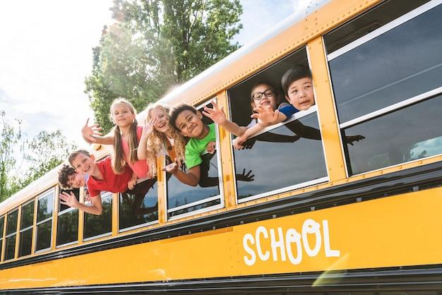 黄色いスクールバスで小学校に通う若い学生のグループ-楽しい小学生