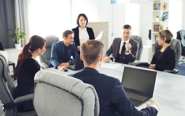 일하는 동안 회의실에서 함께 의사 소통하는 젊은 성공적인 사업가 변호사 그룹...