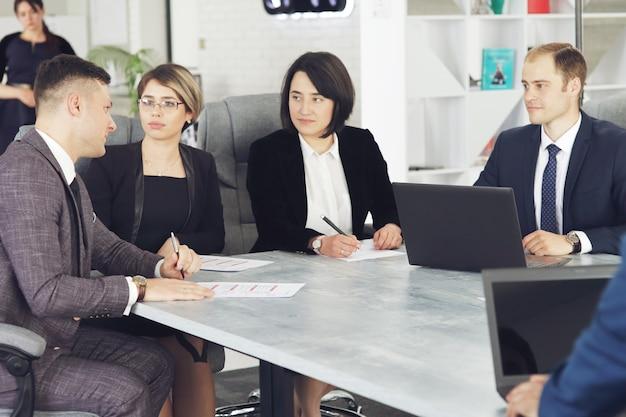 プロジェクトに取り組んでいる間、会議室で一緒に通信する若い成功したビジネスマンの弁護士のグループ