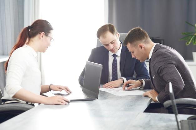 Группа молодых успешных бизнесменов-юристов, общающихся в конференц-зале во время работы над проектом