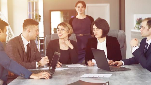 프로젝트를 진행하는 동안 회의실에서 함께 의사 소통하는 젊은 성공적인 사업가 변호사 그룹.