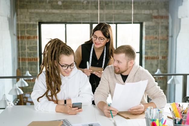 Группа молодых успешных дизайнеров одежды сидит за столом, обсуждая новые творческие идеи на стартовой встрече