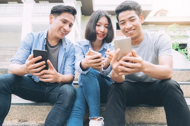 Группа молодых подростков с помощью мобильных телефонов.