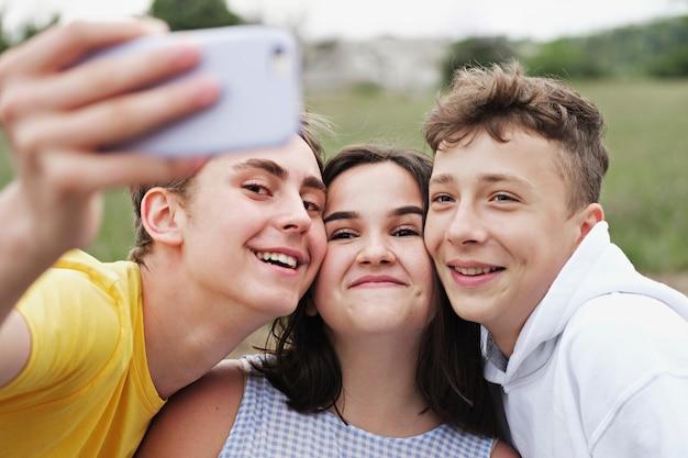 Selfieを取る若い10代の友達のグループ
