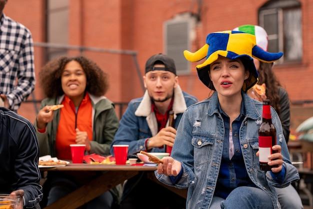 余暇に放送を見て飲み物とスナックを見て緊張した若いフレンドリーなサッカーファンのグループ