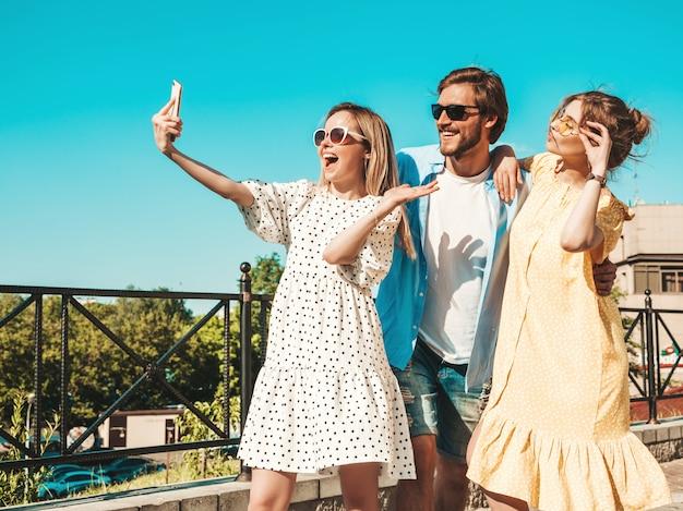 Группа молодых трех стильных друзей на улице. мужчина и две милые девушки, одетые в повседневную летнюю одежду. улыбающиеся модели весело в солнцезащитные очки. женщины и парень, делая фото селфи на смартфоне