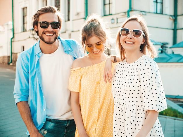 通りでポーズをとる若い3人のスタイリッシュな友人のグループ。ファッション男とカジュアルな夏服を着た2人のかわいい女の子。サングラスで楽しい笑顔のモデル。陽気な女性とサスネットで男