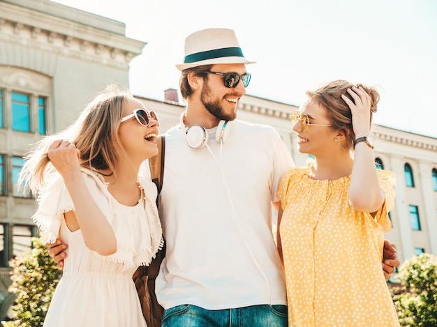 Группа молодых трех стильных друзей позирует на улице. мода мужчина и две милые девушки, одетые в повседневную летнюю одежду. улыбающиеся модели с удовольствием в солнцезащитных очках. веселые женщины и парень в чате