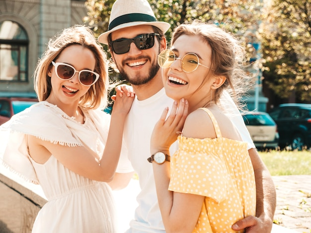 Группа молодых трех стильных друзей позирует на улице. мода мужчина и две милые девушки, одетые в повседневную летнюю одежду. улыбающиеся модели веселятся в солнечных очках. веселые женщины и парень сходят с ума