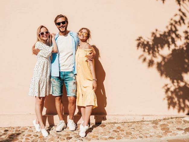 通りでポーズをとる若い3人のスタイリッシュな友人のグループ。ファッション男とカジュアルな夏服を着た2人のかわいい女の子。サングラスで楽しんでいる笑顔のモデル。陽気な女性と男が夢中になる