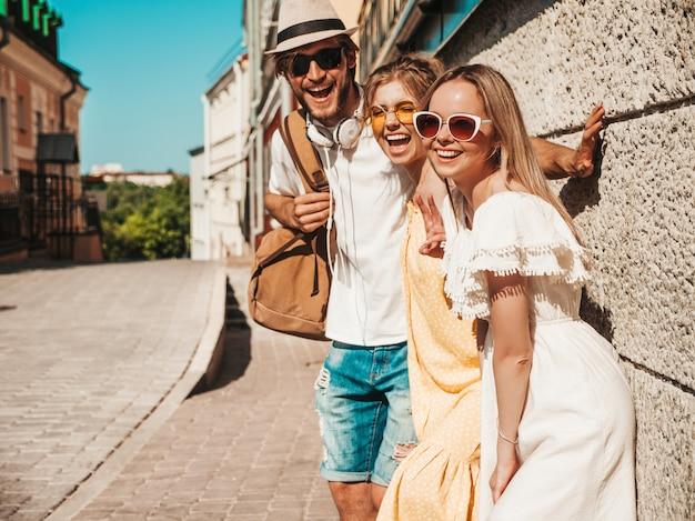 Группа молодых трех стильных друзей позирует на улице. мода мужчина и две милые девушки, одетые в повседневную летнюю одежду. улыбающиеся модели с удовольствием в солнцезащитные очки. веселые женщины и парень на открытом воздухе