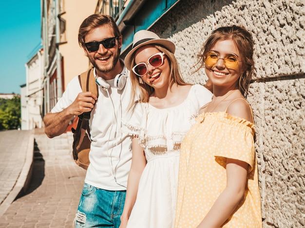 通りでポーズをとる若い3人のスタイリッシュな友人のグループ。ファッション男とカジュアルな夏服を着た2人のかわいい女の子。サングラスで楽しい笑顔のモデル。陽気な女性と男は舌を示す