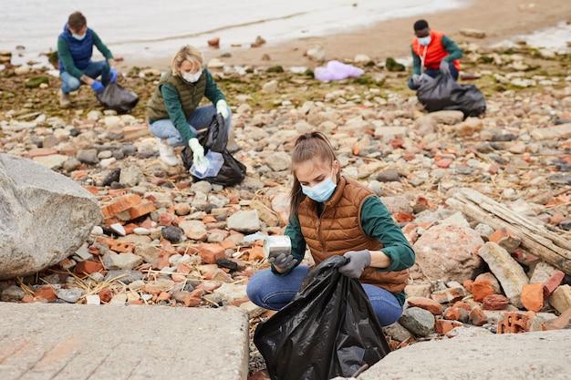 屋外の海岸線近くのバッグにゴミを拾う若いボランティアのグループ