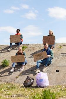 屋外で段ボールのプラカードを持って岩の上に座っている若いボランティアのグループ