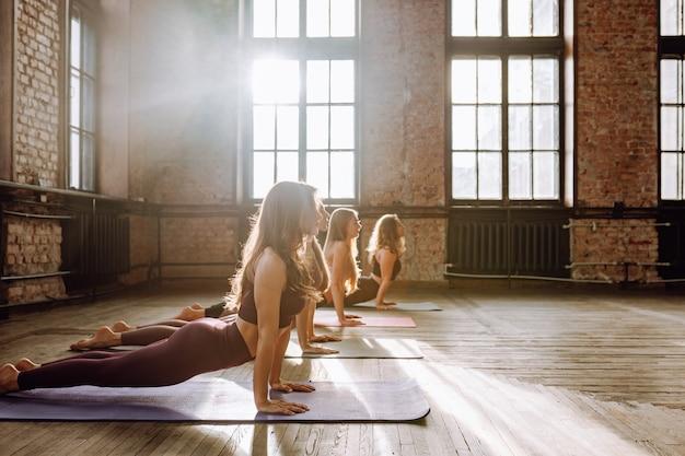 Группа молодых женщин выполняет комплекс асан йоги на растяжку в классе в стиле лофт в солнечный день.