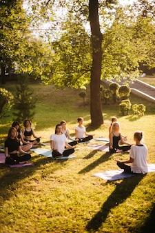 젊은 여성 그룹은 강사의 지도 하에 여름 화창한 아침에 도시 공원에서 명상을 합니다. 평화로운 사람들의 그룹은 눈을 감고 잔디에 연꽃 포즈로 앉아서 야외에서 명상을 하고 있습니다