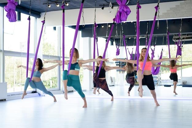 若い女性のグループは、エアロストレッチスイングで練習します。空中飛行ヨガの練習は、フィットネスクラブの紫色のハンモックで練習します。