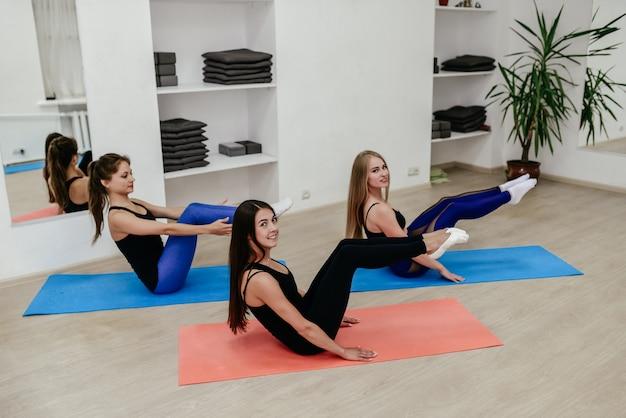 Группа молодых женщин, практикующих йогу в светлой комнате
