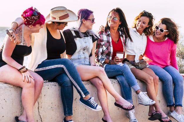 ミレニアル世代の多様性の概念の人々のためのピンクと紫の髪-一緒に話し、幸せと笑顔でレジャーアウトドア活動を座って楽しんでいる若い女性のグループ
