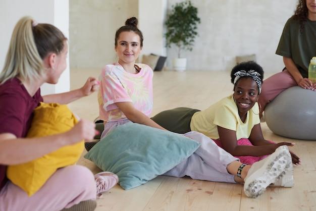 서로 이야기하고 스포츠 홀에서 훈련 후 휴식하는 바닥에 앉아있는 젊은 여성 그룹
