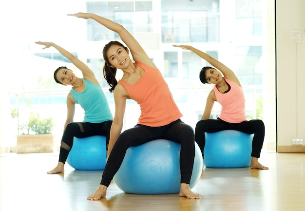 スタジオ、練習、クラス、ヨガ、ボール、体を伸ばしている若い女性のグループ