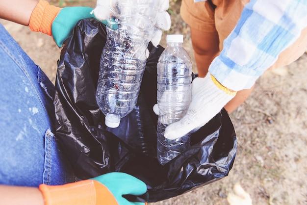 자연을 깨끗하게 유지하고 공원에서 쓰레기 플라스틱 병을 집어 올리는 데 도움이되는 젊은 여성 자원 봉사자 그룹.