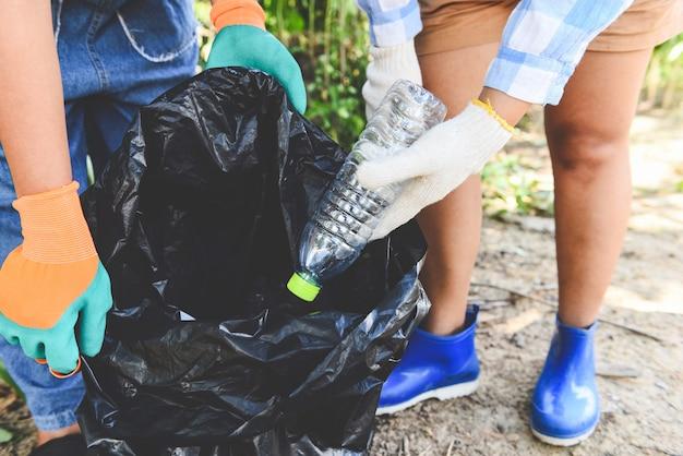 자연을 깨끗하게 유지하고 쓰레기를 줍는 데 도움이되는 젊은 여성 자원 봉사자 그룹