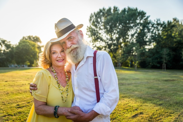 屋外で楽しんでいる若い高齢者のグループライフスタイルと高齢者についての屋外の概念を結合するカップル